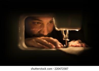 Man at Sewing Machine in a Dimly Lit Room
