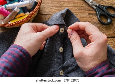 man sews a button to his shirt