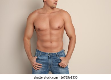 Man with sexy body on beige background, closeup