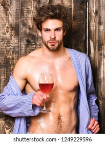 Man sexy chest wet skin after bath hold wineglass. Bachelor enjoy wine after bath. Macho tousled hair degustate luxury wine. Drink wine and relax. Guy attractive relaxing with alcohol drink.