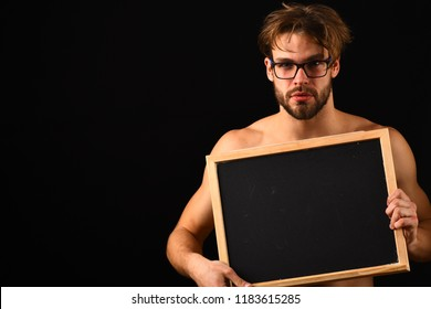 Man sexy muscular torso hold blackboard in front of his naked torso. Macho attractive nude guy hold blackboard. Man with beard and tousled hair black background. Chalkboard advertisement copy space.