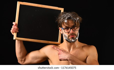 Man sexy muscular torso naked body hold blackboard copy space. Macho attractive nude guy show blackboard. Man bearded tousled hair covered with foam wears eyeglasses. Lack of water. Need take shower.