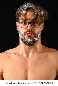 Man sexy muscular torso naked body waist up close up. Macho attractive nude guy black background. Man with beard and tousled hair covered with foam wears eyeglasses. Need take shower. Lack of water.