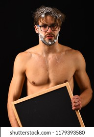 Man sexy muscular torso naked body hold blackboard. Macho attractive nude guy hold blackboard. Man with beard and tousled hair covered with foam wears eyeglasses. Need take shower. Lack of water.