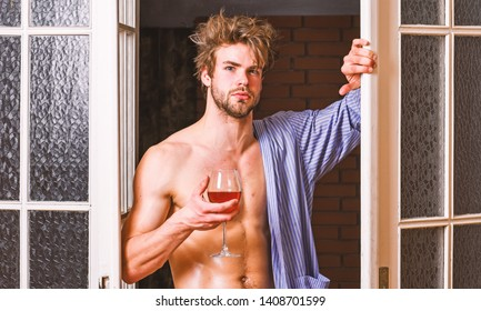 Man with sexy torso drink wine. Sexy lover concept. Bachelor sexy body chest and belly. Guy shimmering sweaty skin wear bathrobe. Sexy attractive macho tousled hair coming out through bedroom door.