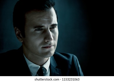 Man in shadow with serious face as a police detective in dark interrogation room