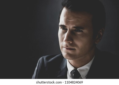 Man in shadow with serious face staring at interlocutor in interrogation room