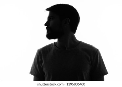 man in the shadows looks to the side