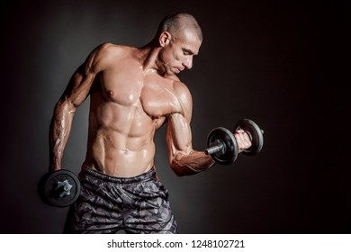 A man shakes his arm muscles. Man with dumbbells. Strong man. Strength exercises. Muscle man. Pumped up muscles. Muscle mass. Dumbbell. Sport equipment.