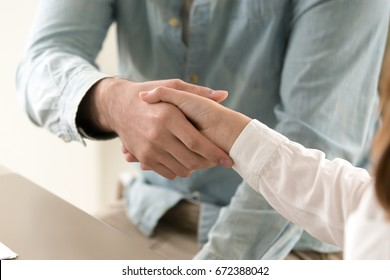Man shaking female hand over the table. Entrepreneurs closing a deal, making agreement. Business greeting, new acquaintance. Successful negotiations or investment, strong working relations