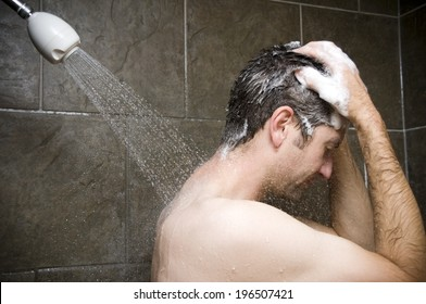 A man shampooing his hair in the shower.