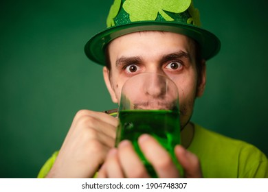 A man in a shamrock hat and green T-shirt drinks a large mug of green ale. Guy celebrates st patrick's day with a glass of beer.