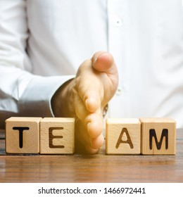 A man shares with his hand cubes with the inscription team. Dividing the collective into two parts or disbanding the team. Lack of leadership qualities and poor quality of business management.