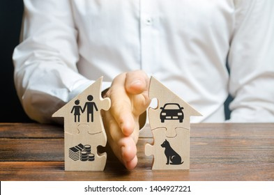 A man shares a house with his palm with images of property, children and pets. Divorce concept, property division process. Marriage contract, custody of children. The layer's services