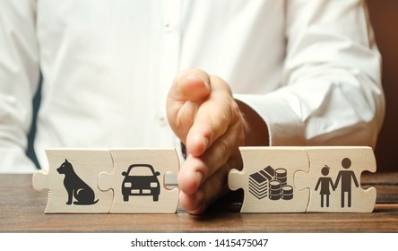A man shares wooden puzzles with images of property, children and pets. The concept of divorce. The process of sharing property. Child custody and parental responsibility. Marriage contract