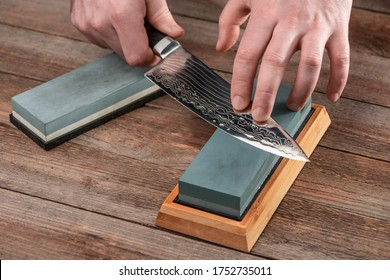 Man sharpening a Japanese chef's knife with a wet whetstone on a rustic wooden table.
