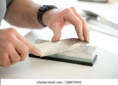 Man sharpening knife in domestic kitchen