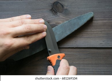 man sharpening survival knife on a sharpener stone. top view on dark background