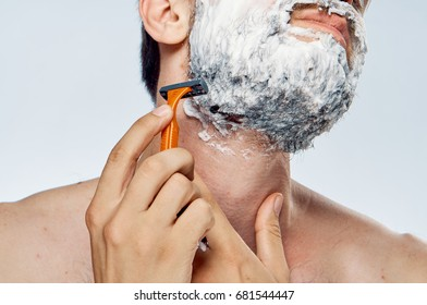 Man shaves beard on light background close-up face care