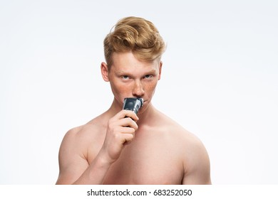 A man shaves his beard on a light background