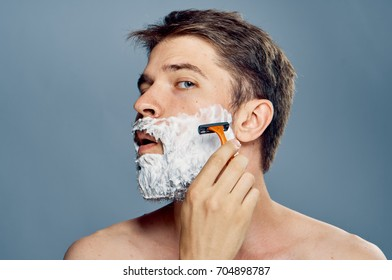A man shaves his beard with a shaving machine on a gray background