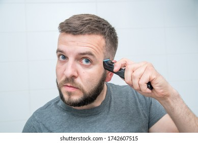 A man shaves his beard with a trimmer in the bathroom