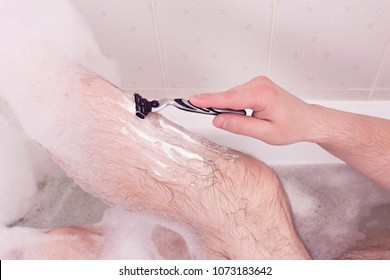 A man shaves his legs in the bathroom.The hand holds the razor.Bath in the foam.