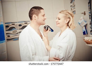 man shaving electrorazor. woman shaves man