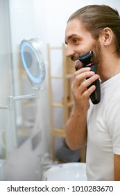 Man Shaving Face, Looking In Mirror. Portrait Of Young Attractive Shaving Beard With Trimmer In Bathroom. Men Face Hair Care. High Quality Image.