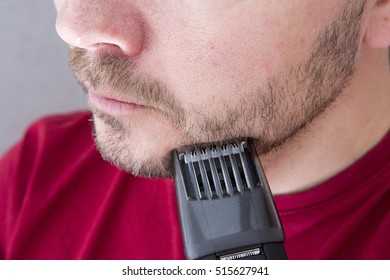 A man is shaving his beard with an electric trimmer.