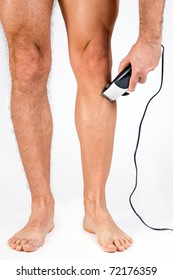 Man shaving his legs. Man shaves his legs with an electric shaver. Male legs shaved with a hair clipper. Cutting hair on a hairy man's legs.