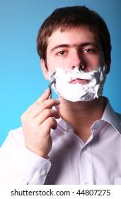Man shaving isolated on blue background