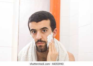 man shaving and looking to the mirror