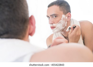 Man shaving in a mirror