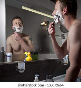 Man shaving with a razor blade in the bathroom