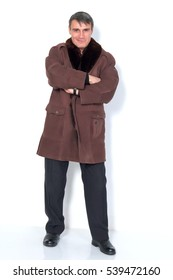 A man in a sheepskin coat in full growth on a light background.