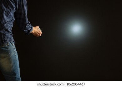 The man shines a flashlight in the dark.