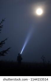 Man shines a flashlight in the night moon sky