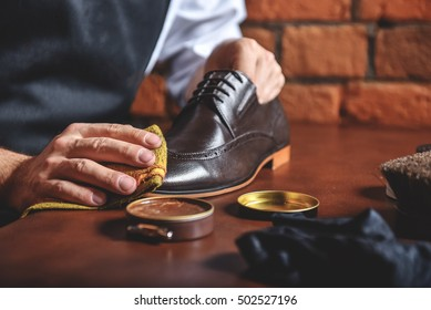 man shining shoes with a rag
