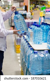 man in shirt choosing, selecting or buying a bottle of mineral drinking or distilling water at the shopping store focus on hands on the supermarket display shelf background