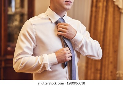 man in shirt dressing up and adjusting tie on neck at home. Men Fashion