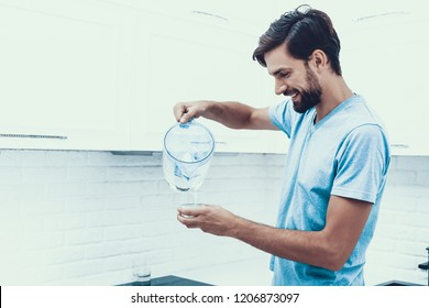Man in Shirt Drinking Water in Kitchen at Home. Healthcare Concept. Fresh Water. Man in T-shirt. Ma in Kitcken. Healthy Drink Concept. Man at Home. Fresh Water. Thirsty Man. Pouring Water.