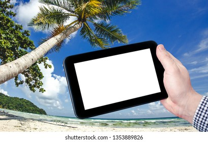 Man in shirt holding empty copy space mobile tablet device with exotic summer beach shore landscape in the background. Searching for holiday offers.