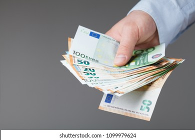 Man in shirt holding euro money in his hands. Banking, salary and donate concept.