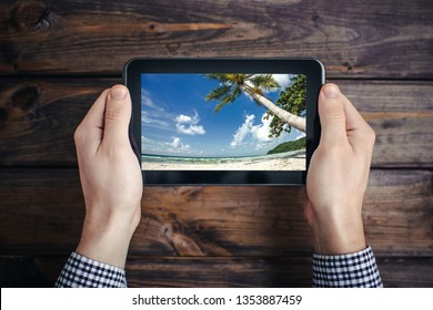 Man in shirt holding mobile tablet device over wooden table. Exotic summer beach shore landscape on a screen. Searching for holiday offers.
