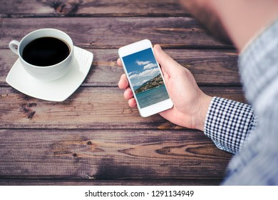 Man in shirt holding smartphone device over wooden table watching beautiful blue sky exotic summer landscape.