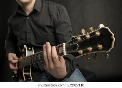 Man in shirt playing black electric guitar