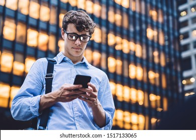 Man in shirt with rolled sleeves and glasses with bag texting on phone standing on background of lighted high building