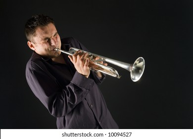 Man in shirt trumpet with might and main. Front view.