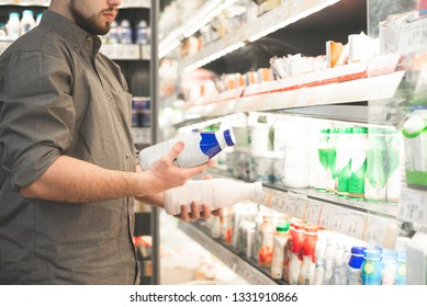 Man in a shirt with two bottles of yogurt in his hands. Buyer is buying a dairy product in a supermarket. Hands of a man with milk close up, background of a light refrigerator with shelves. Copyspace
